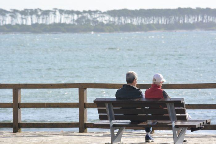 老夫婦がベンチに腰掛け、流れる川を眺めています。