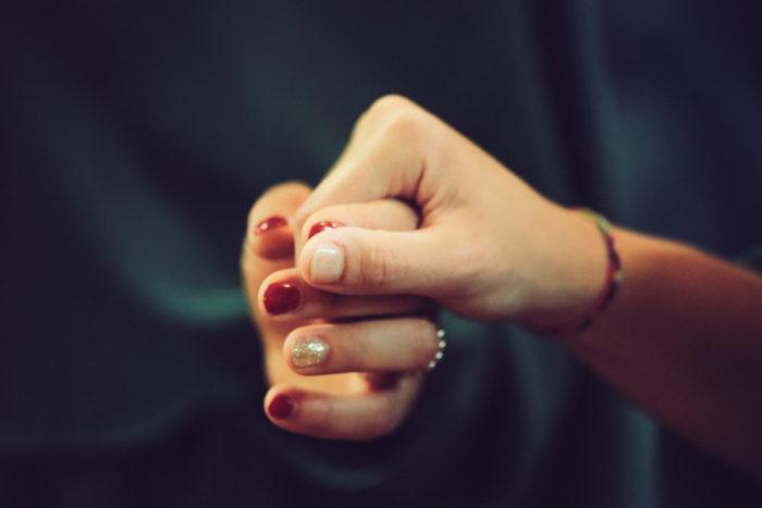 男性と女性が指を絡ませています。男性の手は上にあり、女性の手を軽く握りしめています。